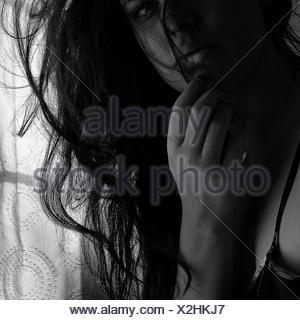 Ritratto di donna con le mani sul mento a casa Foto Stock