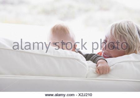 Donna con bambino il peering su divano Foto Stock
