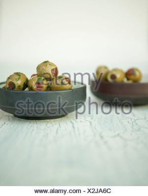 Olive verdi ripiene di peperoncini rossi con olio di oliva e le erbe in una pentola Foto Stock
