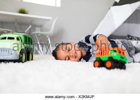 Ragazzo (2-3) giocando con i giocattoli in camera Foto Stock