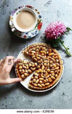 Mano femminile che serve una fetta del dado al caramello crostata con una tazza di caffè Foto Stock