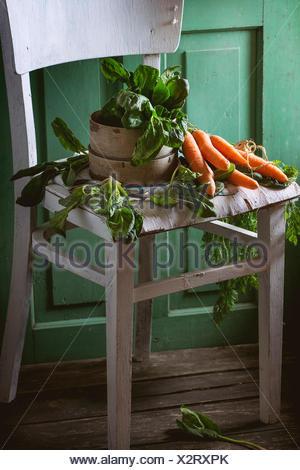 Mazzetto di spinaci freschi e carote sul vecchio bianco sedia in legno verde con pareti in legno a sfondo. Foto Stock
