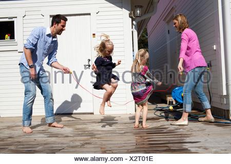 Famiglia saltando la corda Foto Stock