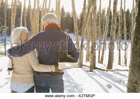 Vista posteriore del giovane camminare attraverso la foresta in inverno Foto Stock