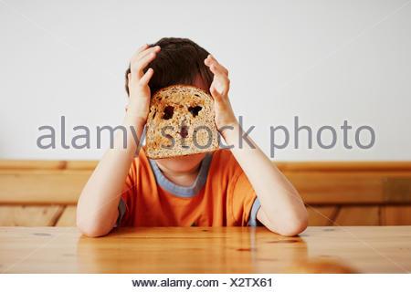 Ragazzo che ricopre la faccia con toast Foto Stock