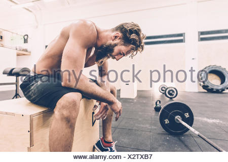 Esaurito croce maschio formatore di prendere una pausa dal sollevamento pesi nella palestra Foto Stock