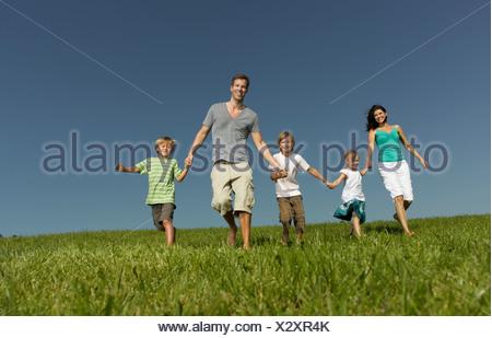 Una famiglia di cinque persone camminando mano nella mano attraverso l'erba Foto Stock