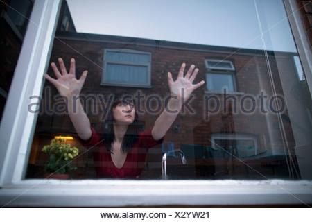 La donna in cucina appoggiata sulla finestra Foto Stock