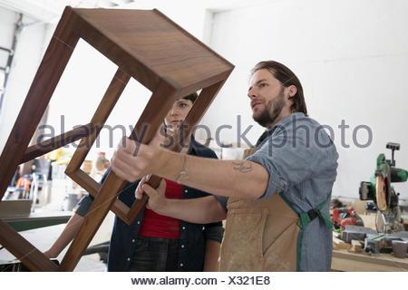 Falegnami serio esame di tavola di legno in officina Foto Stock