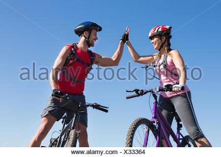 Montare il ciclista giovane permanente al vertice fiving elevata Foto Stock
