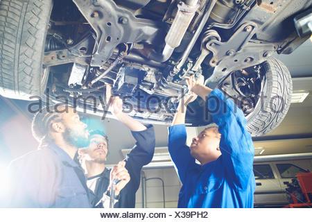 Tre studenti del college che guarda l'auto in garage officina Foto Stock