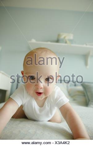 Baby boy strisciando sul letto Foto Stock