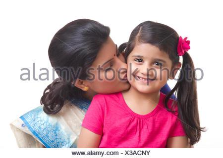Madre baciare la figlia sulla guancia Foto Stock