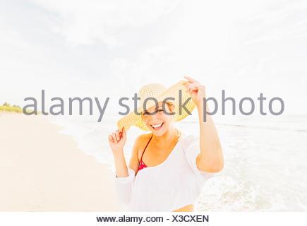 Stati Uniti d'America, Florida, Giove, Ritratto di sorridere giovane donna sulla spiaggia indossando cappello per il sole Foto Stock