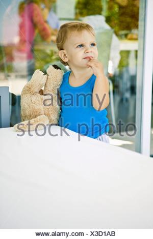 Baby boy tenendo un orsacchiotto di peluche e guardando in alto Foto Stock