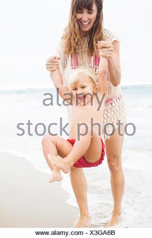 Madre bambino oscillante sulla spiaggia Foto Stock