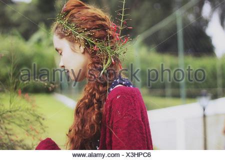 Vista laterale della giovane donna indossa i fiori nei capelli Foto Stock