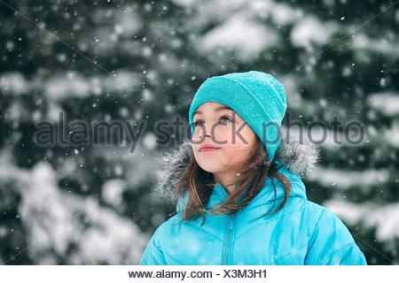 Ragazza indossando knit hat guardando lontano, nevicava Foto Stock