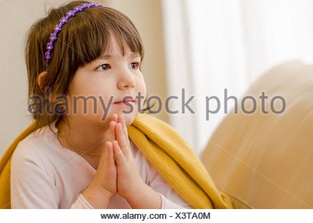Giovane ragazza seduta sul divano fantasticando
