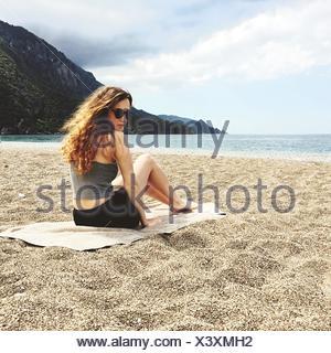 Giovane donna seduta sulla spiaggia con mare contro Sky Foto Stock