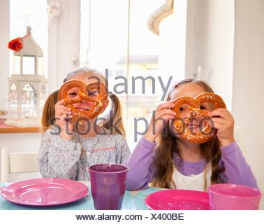 Le ragazze a giocare con il loro cibo in tavola Foto Stock