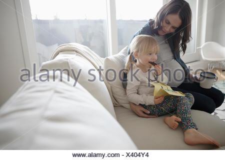 Gravidanza madre e figlia toddler gustando uno spuntino sul divano Foto Stock