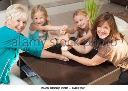 La famiglia felice facendo una pila di Torre delle loro mani e pugni in uno sforzo del team di cooperazione, Baviera, Germania Foto Stock