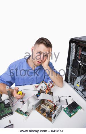 Ritratto di giovane stanco ingegnere informatico con parti cpu su sfondo bianco Foto Stock