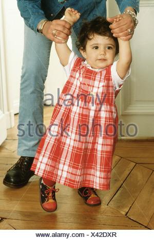 Madre aiutare mia figlia a piedi Foto Stock