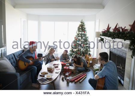 Famiglia riproduzione di chitarre ed incarto di regali di Natale in salotto con albero di Natale Foto Stock