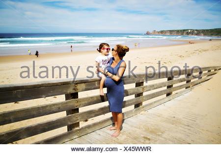 Donna incinta in spiaggia con sua figlia Foto Stock