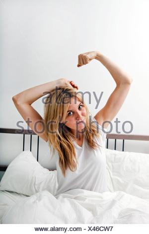 Ritratto di giovane donna stretching nel letto Foto Stock