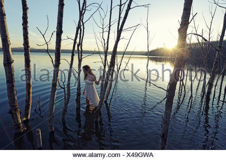 Una ragazza in un abito bianco in acque poco profonde al crepuscolo Foto Stock