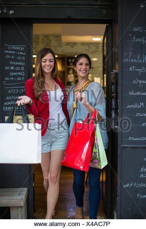 Due giovani amici di sesso femminile lasciando cafe il trasporto delle borse della spesa Foto Stock