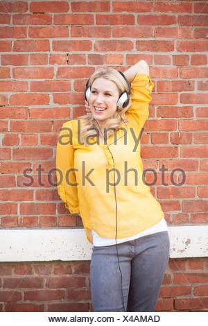 Donna che indossa le cuffie in piedi contro brickwall