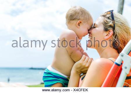 Donna seduta sulla sedia a sdraio con piccolo figlio (18-23 mesi) Foto Stock