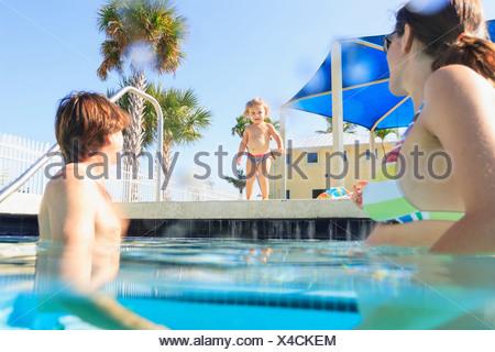 Bambino in esecuzione ai genitori in piscina Foto Stock