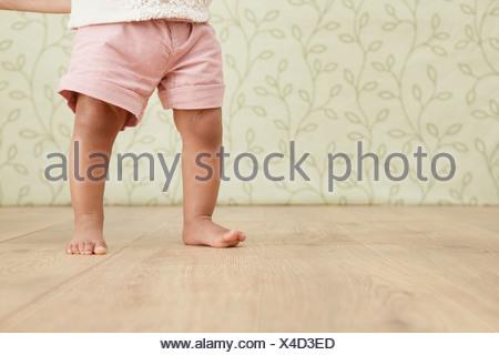 Baby girl prendendo i primi passi, sezione bassa Foto Stock