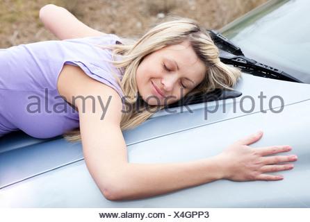 Allegro driver femmina huging la sua nuova vettura Foto Stock