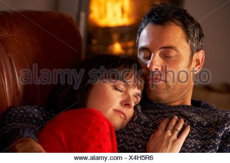 Coppia di mezza età coccole sul divano da caminetto Foto Stock