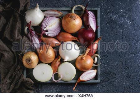 Varietà di interi e fette di rosso, bianco, giallo e scalogno cipolle sulla piazza di legno il vassoio su un letto di sacco rag su pietra scura sullo sfondo di texture. Vista dall'alto,
