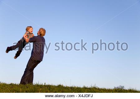 Il padre del ragazzo di filatura nelle sue braccia Foto Stock