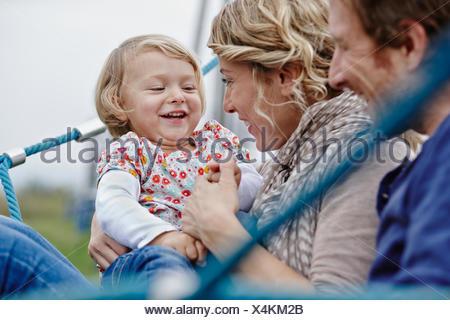 La famiglia felice sul parco giochi in rete da arrampicata Foto Stock