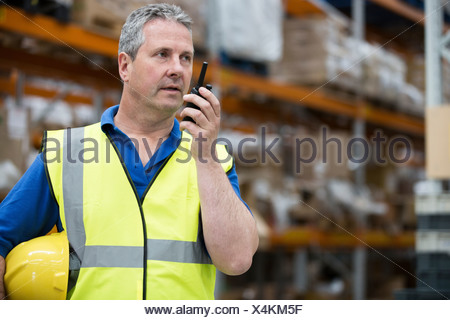 Uomo su walkie talkie in magazzino Foto Stock