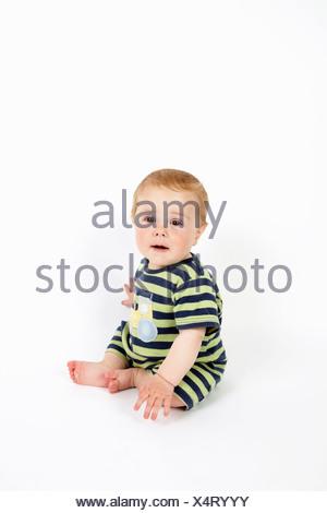 Il Toddler ragazzo seduto sul pavimento Foto Stock