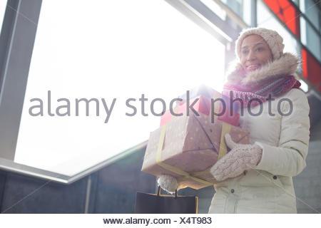 Donna sorridente in un abbigliamento caldo portando doni impilati per finestra Foto Stock