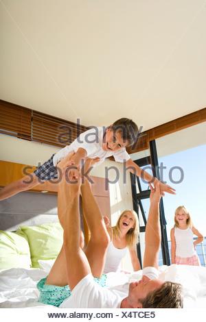 L'uomo sollevamento figlio con le gambe mentre sdraiato sul letto, famiglia in background sorridente Foto Stock