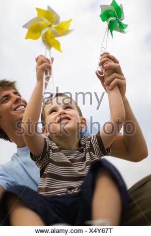 Piccolo Ragazzo seduto sul padre, giro entrambi pinwheels Foto Stock