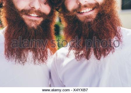 Ritagliato Ritratto di giovane maschio hipster gemelli con la barba rossa indossare magliette di colore bianco Foto Stock