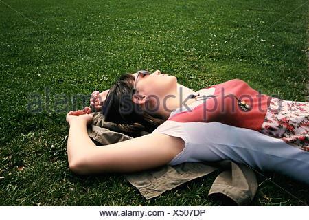 Donna sdraiata su erba rilassante Foto Stock